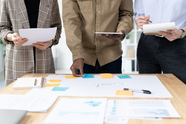 Крупный план неузнаваемой многоэтнической маркетинговой команды, создающей план задач для достижения цели в офисе