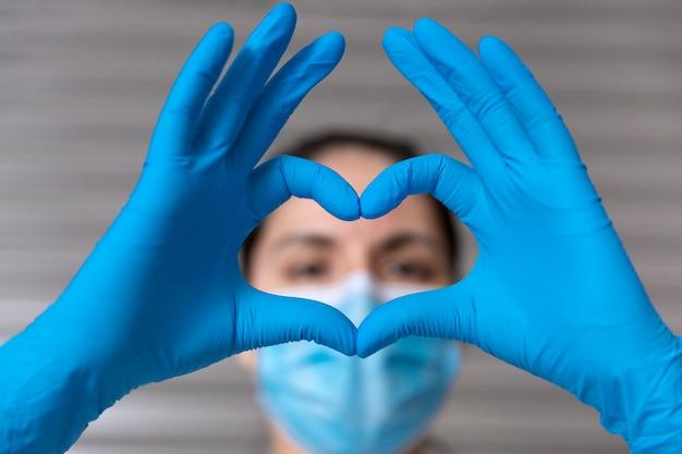 医療用マスクと保護手袋で認識できない看護師のクローズアップ