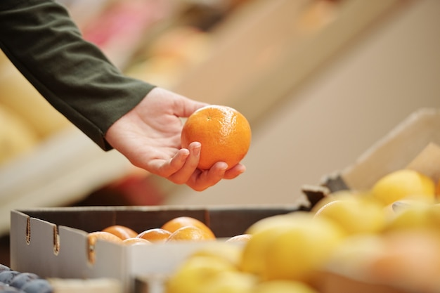有機食品市場、ショッピングコンセプトでみかんを選んでいる認識できない人のクローズアップ