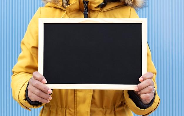 空白の黒板を持っている認識できない人のクローズアップ。 Premium写真