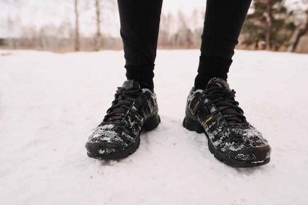 雪の上に立っている冬の黒いスポーツシューズの認識できない人のクローズアップ