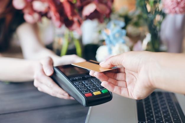 Крупный план неузнаваемого продавца, держащего терминал для бесконтактных платежей в цветочном магазине, покупатель кладет беспроводную карту в терминал