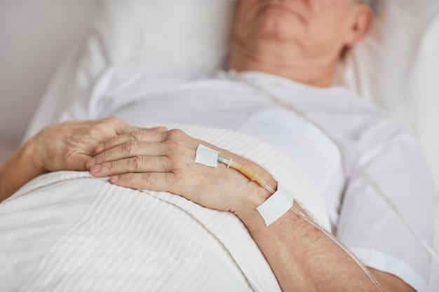 Крупным планом неузнаваемого старшего мужчины, лежащего на больничной койке с акцентом на капельную иглу в руке, копией пространства