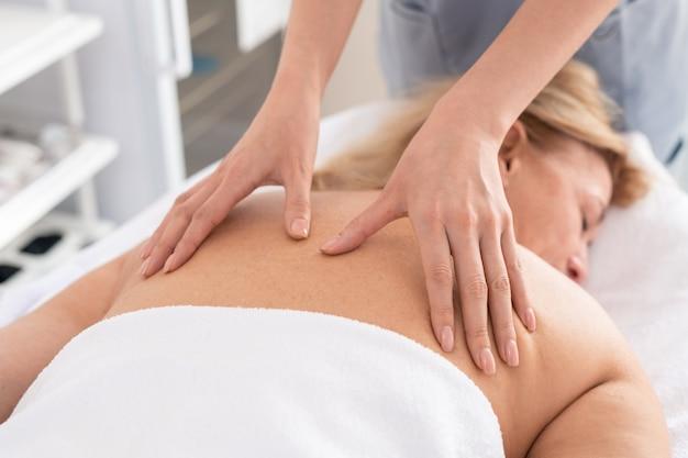 Крупный план неузнаваемого терапевта, делающего расслабляющий массаж спины измученной женщине в спа-салоне