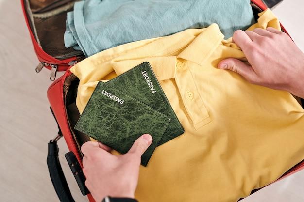 旅行前に荷物を詰めながらスーツケースにパスポートを入れている認識できない観光客のクローズアップ