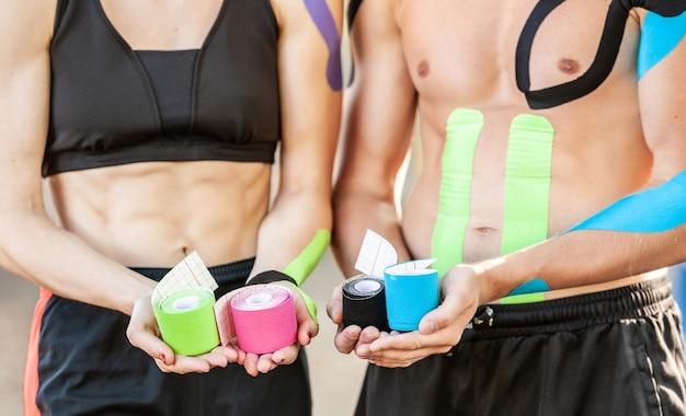 탄성 운동 요법 테이프의 다채로운 롤을 들고 인식 할 수없는 여자와 남자의 닫습니다