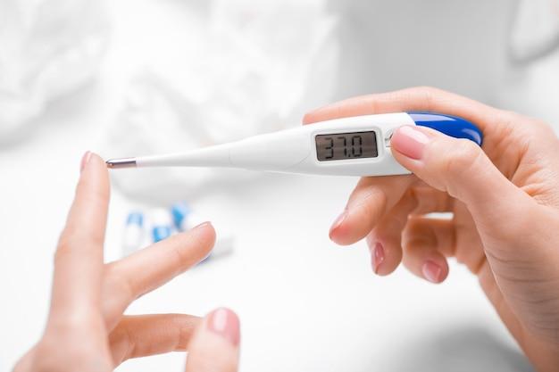 テーブルのデジタル体温計で体温をチェックしている認識できない女性のクローズアップ