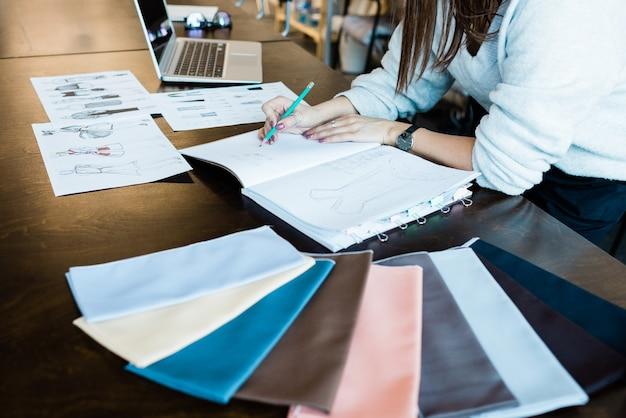 仕立てスタジオで働いている間、メモ帳でファッションスケッチを描いている認識できない女性のクローズアップ