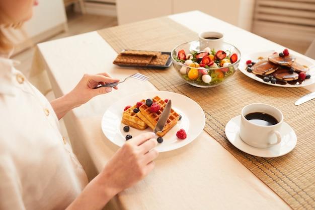Крупным планом неузнаваемой женщины, едящей вкусный десерт, сидя в одиночестве за обеденным столом