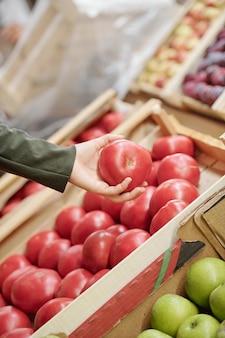 Крупный план неузнаваемой женщины, держащей спелый помидор над прилавком, выбирая его на рынке