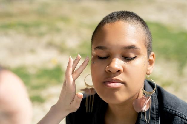 Крупный план неузнаваемой женщины, наносящей блестящий макияж черной девушке на открытом воздухе