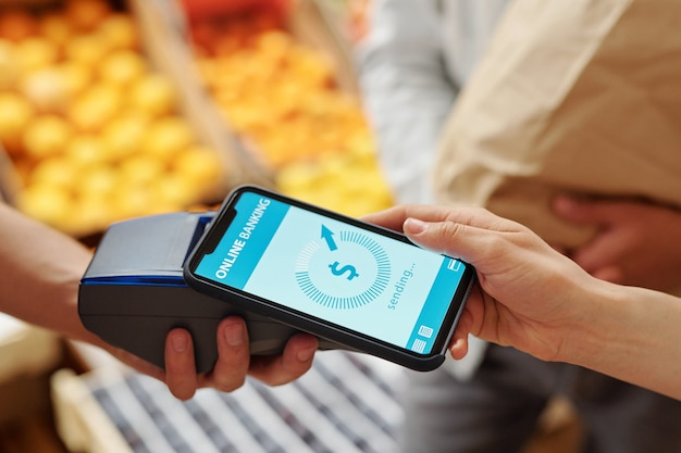 Крупный план неузнаваемой женщины, прикладывающей смартфон к терминалу, оплачивая продукты онлайн на продовольственном рынке
