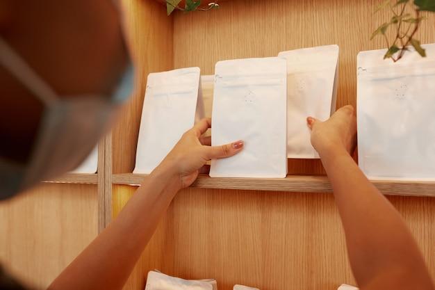 カフェやコーヒーショップ、コピースペースの木製の棚に白いモックアップバッグを置いている認識できない女性のクローズアップ