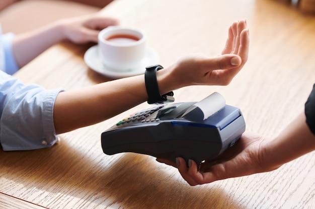 Крупный план до неузнаваемости женщины, прикладывающей наручные часы к платежному терминалу во время бесконтактной оплаты в кафе