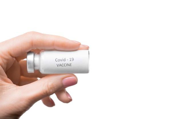 コロナウイルスワクチンのボトルを示す認識できない女性のクローズアップ