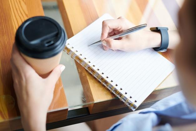 Крупный план до неузнаваемости женщины, сидящей за столом и пьющей кофе, записывая планы и идеи в блокноте