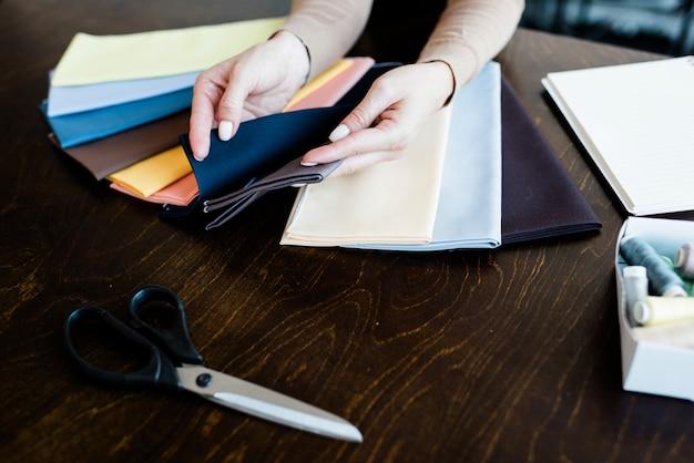 Крупный план неузнаваемой женщины, касающейся выкройки ткани, выбирая ее для шитья