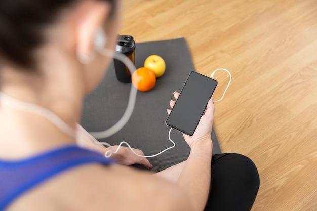 自宅からスポーツを練習しながらスマートフォンを使用して認識できない女性のクローズアップ。テキスト用のスペース。