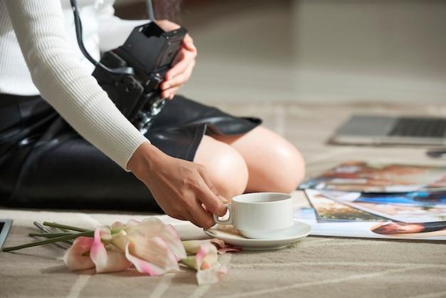 床に座って、印刷された写真で作業しながらコーヒーを飲むビンテージカメラと認識できない女性のクローズアップ