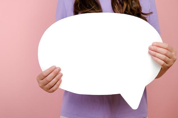 認識できない若い白人女性のクローズアップは、ピンクのスタジオの背景の壁の上に分離された、プロモーションコンテンツのコピースペースと白い空白の吹き出しを示しています。広告エリアのモックアップ