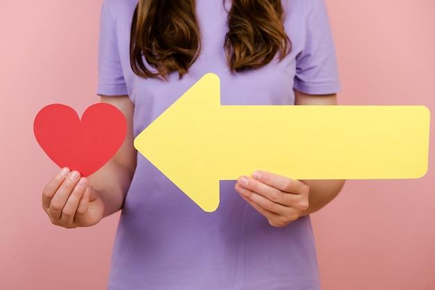 알아볼 수 없는 젊은 여성의 클로즈업은 분홍색 배경에 격리된 작은 빨간색 하트와 노란색 화살표를 보유하고 있습니다. 블로그 블로그 소셜 네트워크 부드러움 개념처럼. 발렌타인 데이 국제 여성
