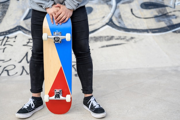 公園でロングボードやスケートボードを保持している認識できない若い男のクローズアップ。