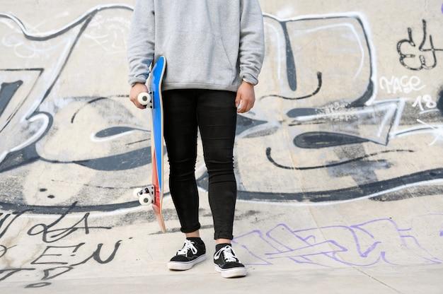 公園でスケートボードを持って認識できない若い男のクローズアップ。