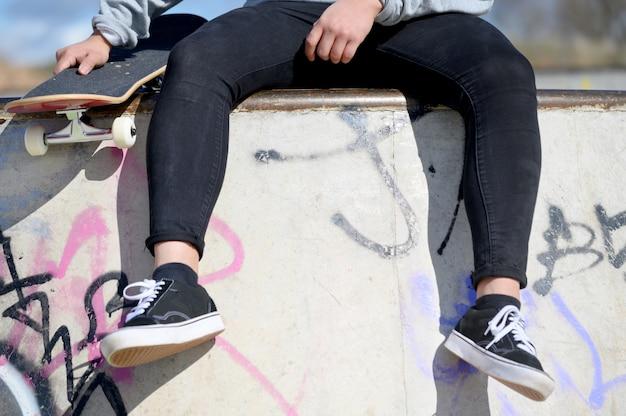 公園でスケートボードに座っている認識できない若い男のクローズアップ。