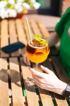 Крупный план до неузнаваемости молодой женщины, держащей стакан с холодным экзотическим коктейлем, сидя за столом в открытом кафе в солнечный летний день. довольно студентка битник, пить прохладный лимонад через соломинку.