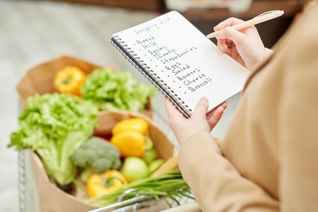 Крупный план неузнаваемой молодой женщины, держащей список покупок при покупке продуктов на фермерском рынке или в супермаркете