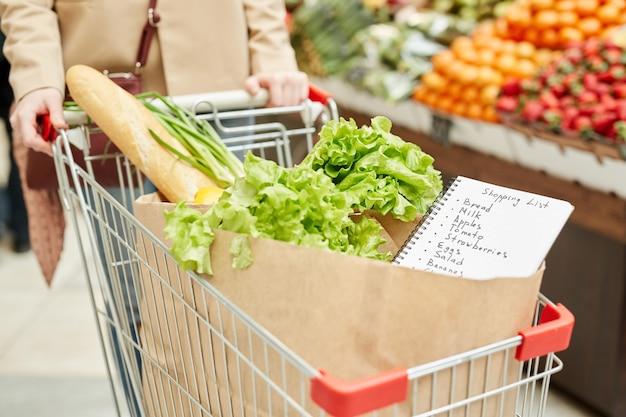 Крупный план неузнаваемой молодой женщины, толкающей тележку для покупок при покупке продуктов на фермерском рынке или в супермаркете
