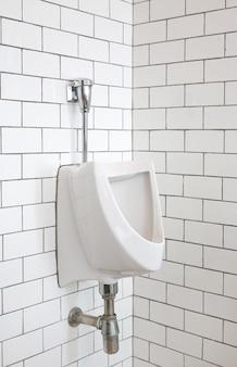 公衆トイレの男性用小便器のクローズアップ。