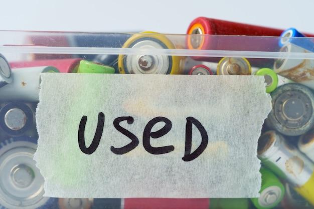 Закройте использованные разряженные батареи в пластиковой коробке на белом фоне. разделение отходов. электронные опасные отходы, концепция утилизации