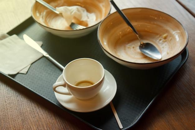 昼食後の食器のクローズアップ。空の皿、一杯のコーヒー、テーブルのキッチントレイにある清潔で汚れたナプキン。ウェブサイトまたはバナーの背景。コピースペース