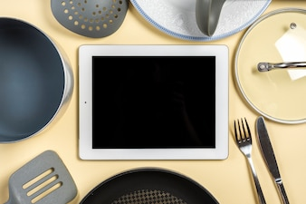 Close-up of utensil around the digital tablet on beige background