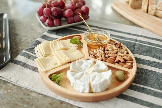 냅킨 식탁에 배치 나무 접시에 다양한 치즈와 견과류 간식의 근접