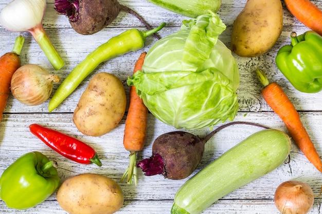白い木製の背景にさまざまなカラフルな生野菜のクローズアップ。