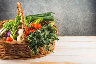 Close-up of various fresh vegetables in wicker basket on wooden background