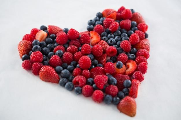 白い背景にハートの形を形成するさまざまな果物のクローズアップ