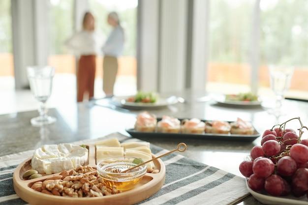 ダイニングテーブルの前菜、チーズ、ブドウなどのさまざまなスナックのクローズアップ