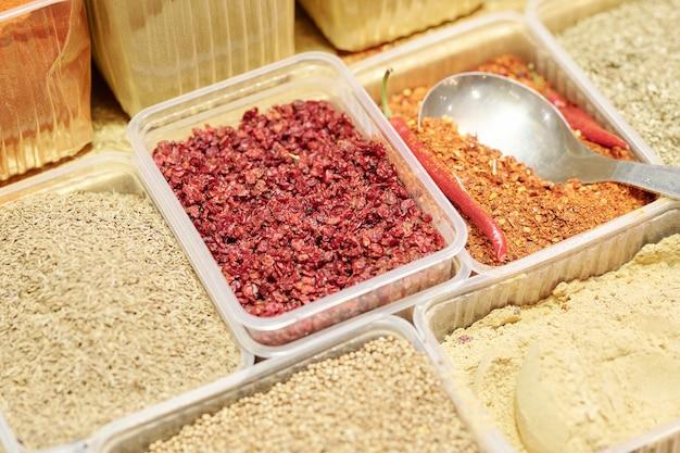 食品市場でおいしい料理を調理するために使用される使い捨て容器内のさまざまなスパイスのクローズアップ