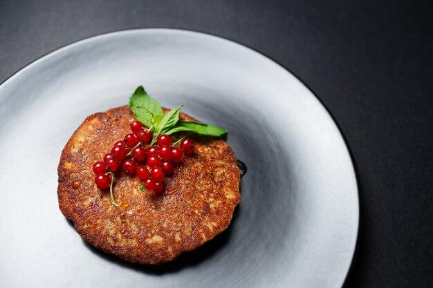 テクスチャード加工の丸いプレートに赤スグリを添えたビーガン自家製パンケーキのクローズアップ。