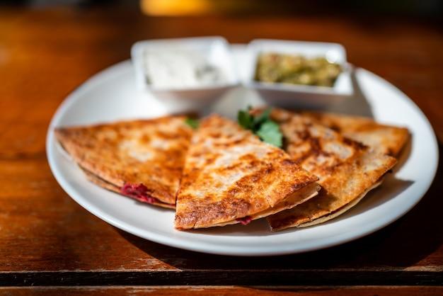 ビーガンケサディーヤのクローズアップ:サツマイモと小豆を詰めた全粒小麦のトルティーヤのグリル、ワカモレとツァジキソース添え。