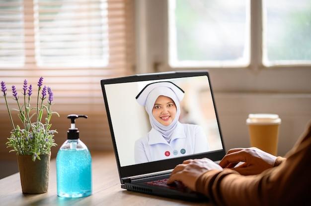 男性医師とデスクでのラップトップのビデオ会議のクローズアップ、ヘルスケアの概念