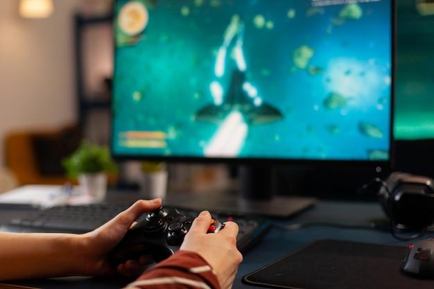 Крупным планом видео-геймер, использующий беспроводной контроллер во время турнира по космическим стрелялкам в игровой домашней студии. профессиональный профессиональный игрок, транслирующий новую графику онлайн-видеоигр с помощью мощного компьютера