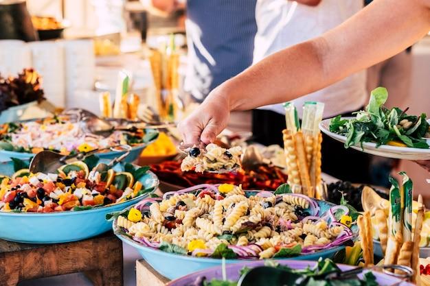 Крупным планом вид на стол, полный еды, с кем-то, кто берет пасту со стола, чтобы отпраздновать