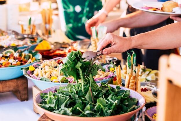 Крупным планом вид стола, полного еды, с кем-то, кто берет овощи со стола, чтобы отпраздновать