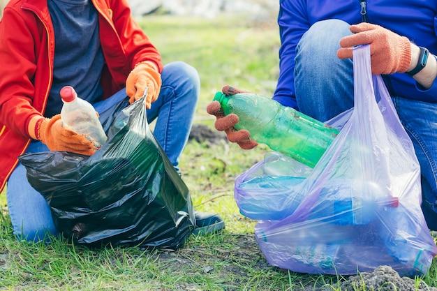 공원과 숲에서 쓰레기를 줍는 자원 봉사자 남자와 아들의 클로즈업 생태학 개념 두 사람의 손이 플라스틱 병을 쓰레기 봉투에 넣습니다