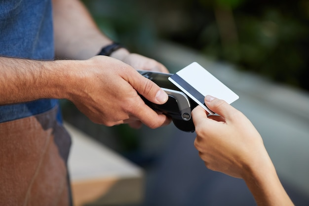 Крупный план официанта, держащего платежный терминал, пока женщина использует свою кредитную карту
