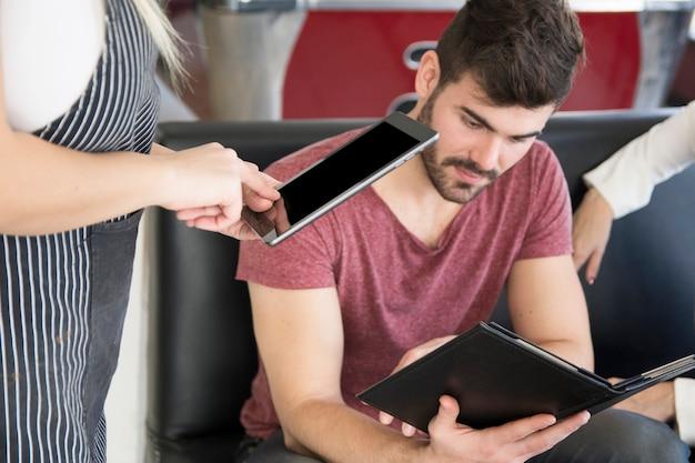 디지털 태블릿에 고객 주문을받는 웨이트리스의 클로즈업